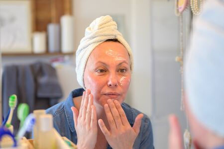 Woman applying skin cream or moisturiser to her face with focus to her reflection in the bathroom mirror in a skincare and ageing concept Standard-Bild