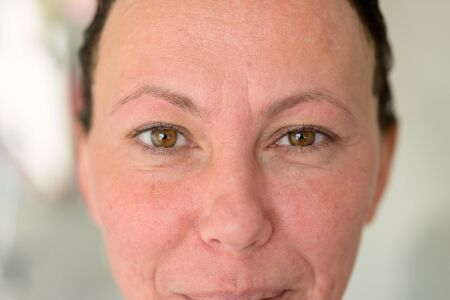 Woman with laughing brown eyes in close up as she looks directly at the camera in a cropped portrait