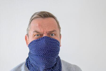 Middle-aged man in blue wrap over his face with anxious and mistrustful look, staring fearful Banque d'images