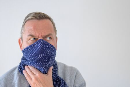 Middle-aged man in blue wrap over his face with anxious and mistrustful look, staring aside to the copy space on blue background