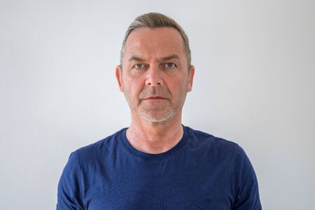 Bust front portrait of middle-aged man in blue t-shirt isolated against grey background and looking at camera with calm emotionless face