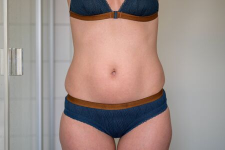 Midriff of a slim 38 year old woman in underwear posing in a bathroom showing her bare stomach and hips in a weight and healthy diet concept