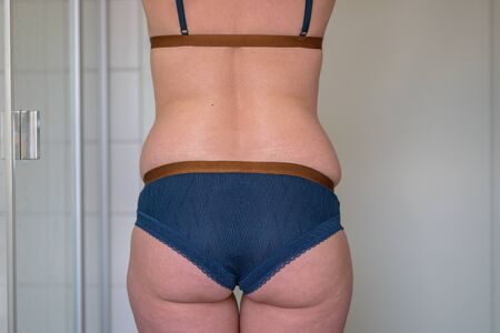 Rear view of the midriff and buttocks of a 38 year old woman in underwear posing in a bathroom in a concept of weight and healthy diet