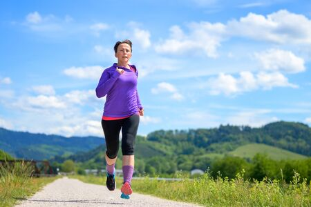 Woman jogging along a country road in spring sunshine during her daily workout in a low angle view for fitness and active lifestyle concepts