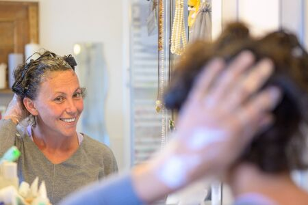 Woman coloring her hair with hair dye at home smiling at herself in the bathroom mirror with focus to the reflection
