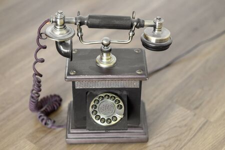 Old vintage telephone with handset on cradle above a numbered dial viewed high up on a wooden table in a communications concept