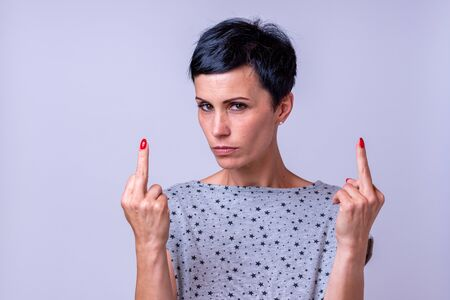 Attractive woman making a derogatory middle finger gesture with both hands pointing to herself while looking thoughtfully at the camera over a grey background