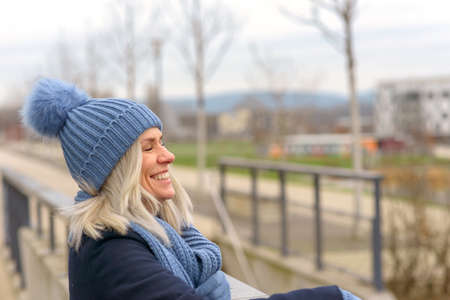 Joyful blond woman in a warm winter outfit with woolly hat and scarf standing outdoors looking to the side over urban buildings grinning happily