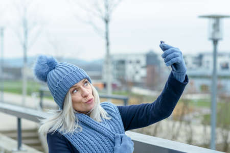 Charismatic stylish woman in a warm woolly blue winter outfit taking a selfie on her mobile phone outdoors in an urban environment