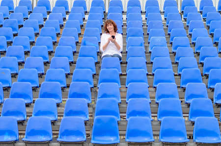Lone middle-aged woman in a stadium sitting in the center of rows of empty blue seating chatting on her mobile phone