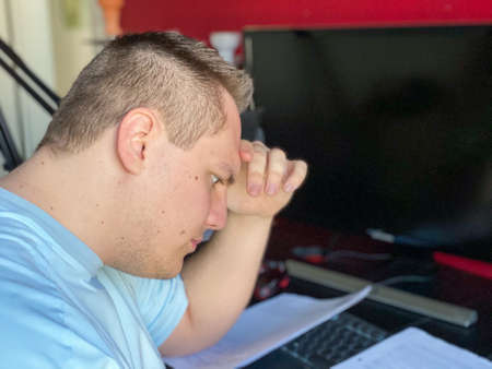 Young man sitting reading a document with engrossed concentration resting his head on his hand as he reads