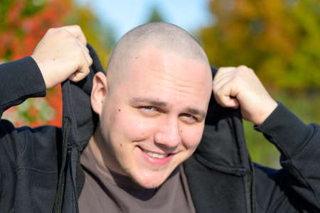 Smiling friendly young man adjusting his collar of his casual black top outdoors in warm fall or autumn sunshine in a close up portrait looking at the camera