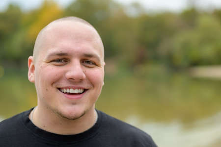 Happy casual young man with shaved head standing outdoors in a park near a lake laughing at the camera with copyspace Фото со стока
