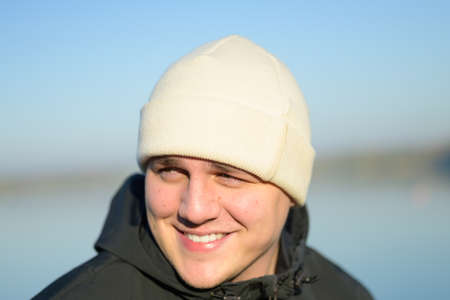 Happy friendly young man with a lovely warm smile posing outdoors in a knitted beanie hat and warm jacket in autumn looking aside Stock Photo