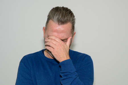 Despondent middle-aged man holding his head in his hand covering his eyes as he looks down dejectedly against a white studio wall