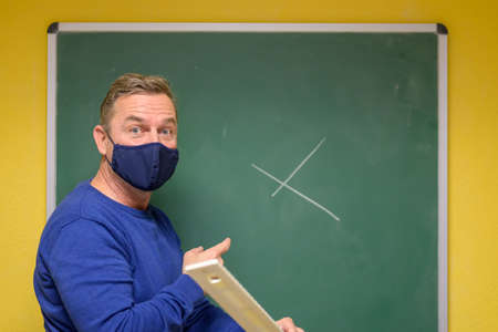 Teacher wearing a face mask during pandemic turning expectantly to his class with a quizzical expression after starting to write on a class chalkboard
