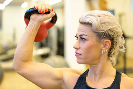 Fit muscular woman working out with a kettle weight in a gym in a health and fitness concept lifting it above her shoulder in close up profile view