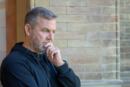 Man standing outside a brick building deep in thought with his hand to his chin and a contemplative expression facing to the side and copyspace