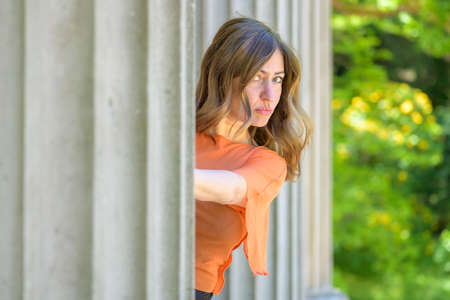 Playful stylish middle-aged woman peering around a fluted historic outdoor column with teasing look and pursed lips Imagens