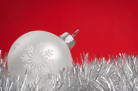 White Christmas bauble over red background