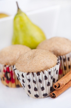 Three muffins on white plate with pear in the background, selective focus Stock Photo