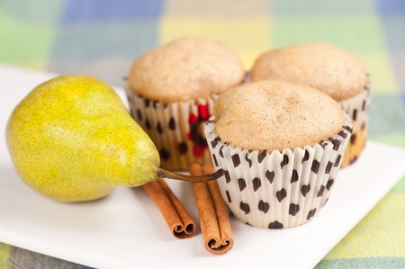 Three muffins on white plate with pear and cinnamon, selective focus