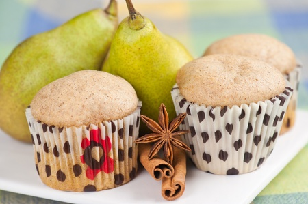 Three muffins on white plate with pears,cinnamon and anise, selective focus Stock Photo