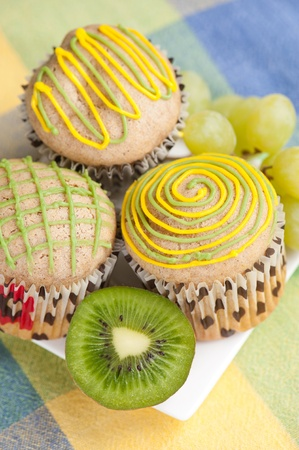 Three muffins on white plate with grapes and kiwi, selective focus Stock Photo - 12442002