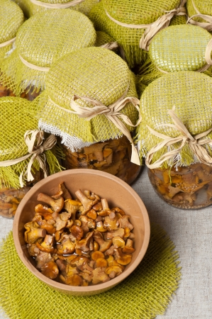 Marinated golden chanterelles in jars and in a bowl Stock Photo