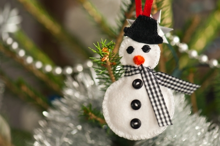 Handmade of felt snowman hanging on a Christmas tree