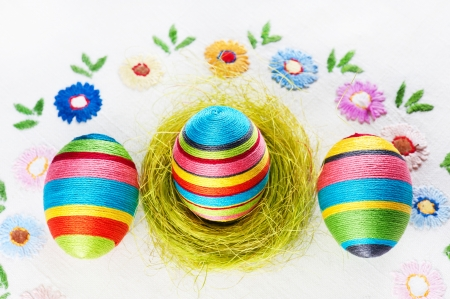 Handmade Easter eggs on an embroidered tablecloth photo