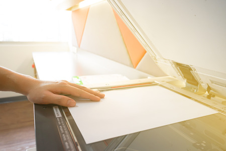 copying: Man copying paper from Photocopier sunlight from window Stock Photo