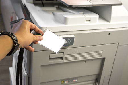 xerox: man hand hold card for scanning key card to access  Photocopier . Security system concept.