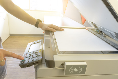 xerox: Man copying paper from Photocopier with access control for scanning key card sunlight from window Stock Photo