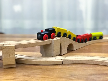 Wooden toy train on wooden rail.