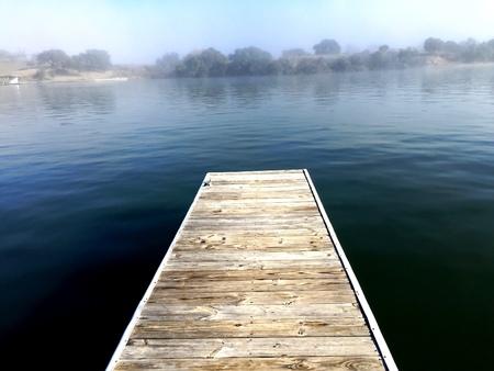 Dock overlooking calm fog on the river Фото со стока