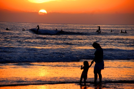 Mother and daughter holding hands on the beach in the sunset Banco de Imagens