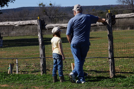 Girl with grandpa leaning on a fence in a pasture