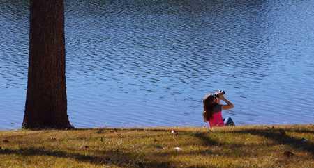 Girl looking through binoculars  by the riverside