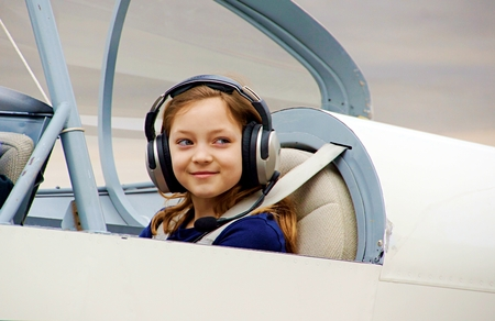 Girl sitting in two seater airplane smiling and ready to fly Banco de Imagens
