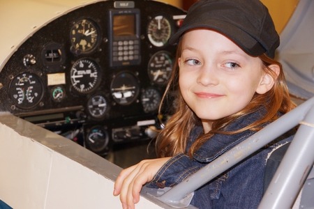 Girl sitting in cockpit of airplane smiling and ready to fly