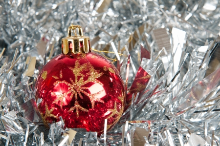 Small red christmas ball over silver tinsel