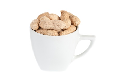 Peanuts in a white cup against a white background