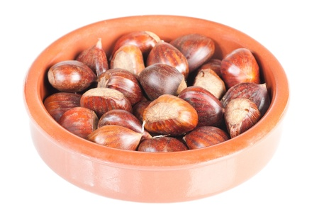 Chestnuts in a rustic bowl over a white background