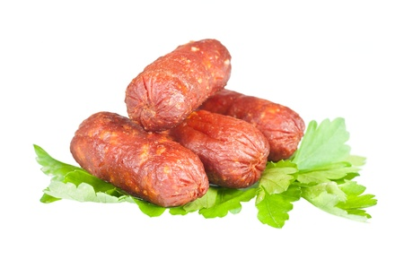 Small sausages on a white background with green parsley Stock Photo