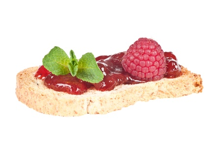Roasted bread with jam or marmelade garnished with mint and raspberry Stock Photo