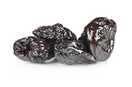 Dried prunes over a reflective white background Stock Photo