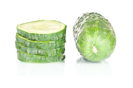 Sliced cucumber vegetable over a reflective white background
