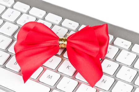 Modern computer keyboard with red bright bow. Stock Photo