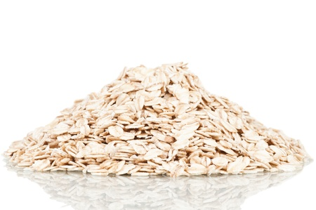 Oat flakes over a white reflective background Stock Photo